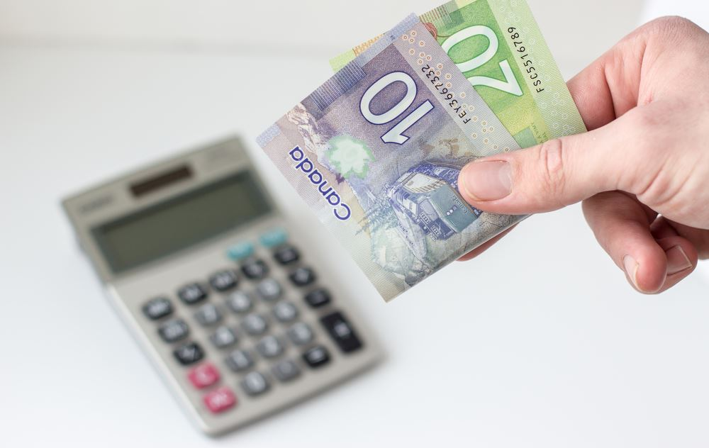 Here's Why Some Canadians Are Cutting Currency in Half