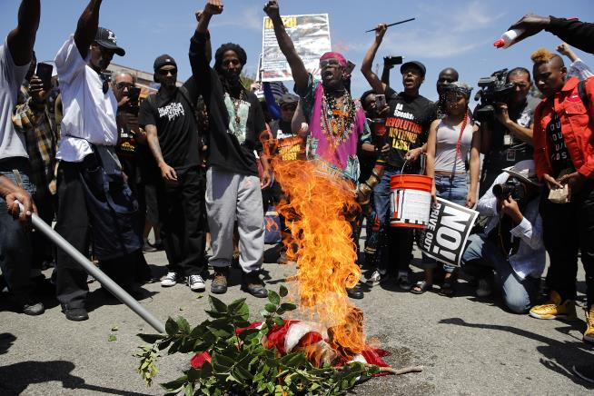 Maxine Waters supporters burn the American flag during counter protest