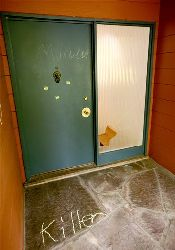 Graffiti and a broken window mark the doorway of the home of a University of California professor, following a demonstration by animal rights activists on Saturday, May 31, 2008, in Berkeley, Calif.