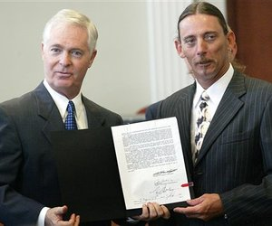 North Carolina Gov. Mike Easley and Mark Lunsford hold the newly-signed Jessica's Law in Gastonia, N.C. on July 28, 2008.