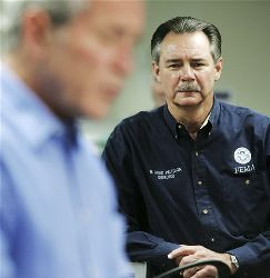 FEMA Administrator David Paulison, right, listens as President Bush briefs members of the traveling press corps, Sunday, Aug. 31, 2008, at FEMA Headquarters  in Washington.