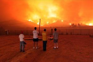 Residents look on as a wind driven Santa Ana fire threatens homes, in Yorba Linda, Calif., yesterday.