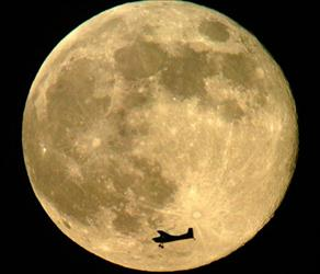 The silhouette of a single engine plane caught in the full moon on Saturday evening over Denver.