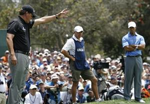 Tiger Woods, right, and his caddie, Steve Williams, look on as Phil Mickelson takes a drop.