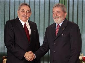 Cuba's President Raul Castro, left, shakes hands with Brazil's President Luiz Inacio Lula da Silva at the presidential palace in Brazil.