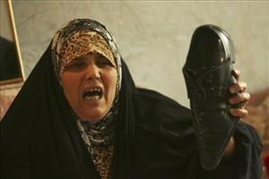 Um Sa'aad, a sister of Iraqi journalist Muntadar al-Zaidi wails as she holds a shoe of her brother at his apartment in in Baghdad, Iraq, Monday, Dec.15, 2008.