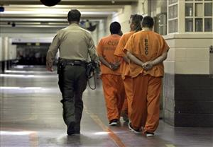 A correctional officer escorts a group of recently arrived inmates in California. Some attribute the rise in murder rates to a migration of prison culture to the streets.