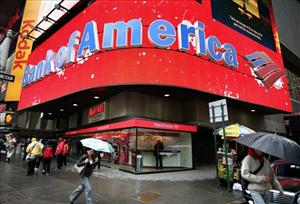 In this Nov. 25, 2008 file photo Pedestrians walk through New York's Times Square under a glowing Bank of America marquee.