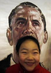 A Chinese girl smiles as she poses for a snapshot with a painting depicting U.S. President-elect Barack Obama, by Chinese artist Yu Chengsong, during an exhibition to mark his inauguration.