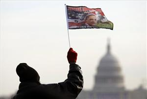 Das Stoked of Providence, RI, waves a flag with the image of President-elect Barack Obama on the National Mall looking towards the US Capitol today.