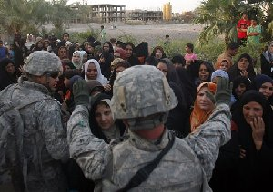 Troops from Alpha Company, 1st Battalion, 5th Cavalry Regiment, 2nd Brigade, 1st Cavalry Division try to organize a group of Iraqi residents that are queued for water and food supplies distributed by the U.S. Army in the Amariyah neighborhood of west Baghdad, Iraq on Monday, Aug. 6, 2007. (AP...