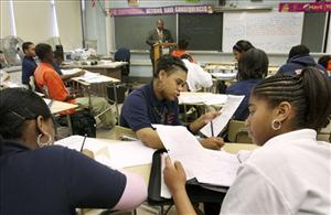 Baltimore  students work together on a math problem while substitute teacher Amon Carter, far back, teaches the class, Wednesday, Dec. 19, 2007, in Baltimore.