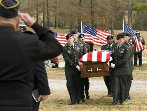 The body of a soldier is escorted by a US Army Honor Guard at his funeral.