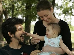 Katie Laird, a 24-year-old Web marketing professional and self-proclaimed social software geek, and her husband Adam Sandoval play with their daughter. Laird met Adam online.