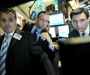 In this 2008 file photo, specialists gather around the post where their firm trades Fannie Mae prior to the opening bell at the New York Stock Exchange.