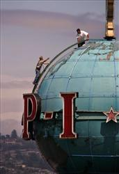 A pair of workers stand atop the landmark globe on the roof of the building housing the 'Seattle Post-Intelligencer' during maintenance work.