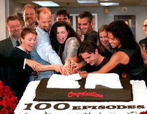 In this Oct. 20, 1998 file photo, cast members of ER celebrate the 100th episode as NBC President Warren Littlefield, second row left, and series creator John Wells, look on.