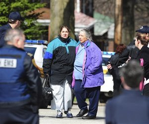 The mother and grandmother of Richard Poplawski leave their home in the Stanton Heights area of Pittsburgh.