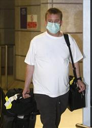 A passenger arrives at Manchester Airport wearing a face mask today. Biden says Americans should avoid flying on airplanes during the outbreak.