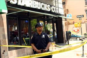 A New York City cop waits at the scene of an early morning bombing at a Manhattan Starbucks.