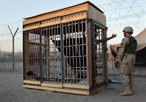 A detainee in an outdoor solitary confinement cell talks with a military policeman at the Abu Ghraib prison on the outskirts of Baghdad, Iraq in this 2004 file photo.
