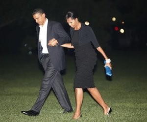 President Barack Obama and his wife first lady Michelle Obama walk together on the South Lawn of the White House as they return from a date in New York City, May 31, 2009.