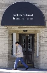 A man walks in front of a real estate loans office in San Mateo, Calif., Friday, Aug. 17, 2007. It's never been tougher to close a deal than during the past few weeks as lenders have gone bankrupt and the skittish survivors become more discriminating to avoid further trouble. (AP...
