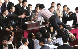 An opposition Democratic Party lawmaker jumps on the podium to block passage of media reform bills as security guards and the ruling Grand National Party's lawmakers block him today.