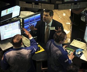 Specialist Igor Lerner of Barclays Capital, center, works with traders on the floor of the New York Stock Exchange in this undated file photo.