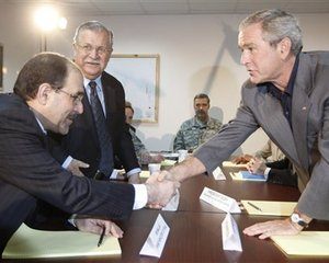 President Bush, right, shakes hands with with Iraq's Prime Minister Nouri al-Maliki, left, as President Jalal Talabani, second from left, looks on at Al-Asad Airbase in Anbar province, Iraq, Monday, Sept. 3, 2007. The president made an unannounced visit to Iraq to meet with Gen. David Petraeus, commanding general of...
