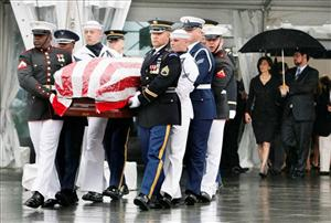 An honor guard carries the casket of Sen. Edward Kennedy from the John F. Kennedy Presidential Library in Boston, followed by Victoria Kennedy.