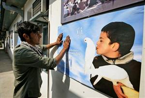An Afghan youth puts up a poster for International Peace Day during its launching ceremony at the office of United Nations Assistance Mission in Afghanistan today.