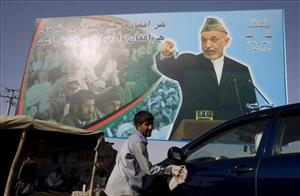 An Afghan cleans a car in front of a poster of Afghan President Hamid Karzai in Kabul, Afghanistan, Saturday, Aug. 29, 2009.