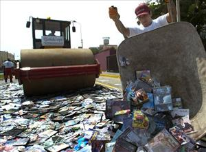 A bulldozer rolls over a pile of pirate CDs, DVDs and software in Lima, Peru.