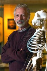 Dr. C. Owen Lovejoy, a member if the team, with a reproduction of Lucy's skeleton.