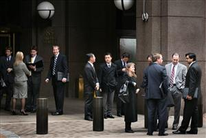 Business people congregate in front of Goldman Sachs headquarters, Wednesday, Oct. 14, 2009 in New York. The bank posted a third-quarter profit of $3.1 billion, beating estimates.