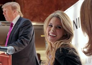Miss California USA, Carrie Prejean, reacts as Donald Trump, left, speaks during a news conference in New York, Tuesday May 12, 2009.