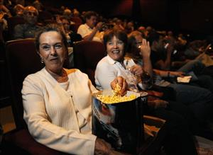 Ellen Gifford, left, sits with popcorn and a soda inside the AMC Burbank 16 theater in Burbank, Calif., Monday, Sept. 22, 2008.