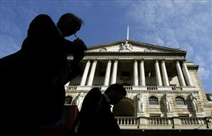 People are silhouetted as they walk past the Bank of England in the City of London.