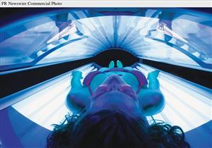 A woman catches some rays in a tanning bed.