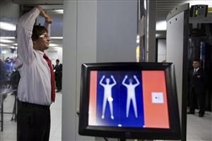 In this photo taken Monday, Dec. 28, 2009, an employee of Schiphol stands inside a body scanner during a demonstration at a press briefing at Schiphol airport, Netherlands.
