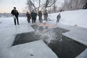 A woman plunges into an icy pond to mark the upcoming Epiphany in Kuzminki park in  southeastern Moscow, Monday, Jan. 18, 2010.