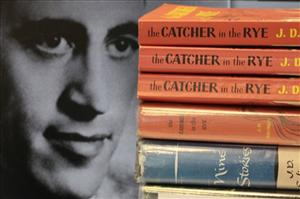 Copies of JD Salinger works are seen next to a 1951 photo of the author at a public library.