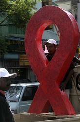 An activist holds a cut-out of a red ribbon, displaying their solidarity with people living with HIV and AIDS,  during a rally marking World AIDS Day in Calcutta, India, Tuesday, Dec. 1, 2009.