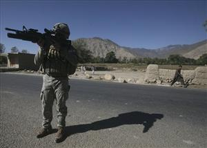 A US soldier looks through his gun as Afghan boy passes by during a patrol in Narang district, eastern Afghanistan, Nov. 4, 2008. Narang was the site of the Dec. 2009 raid.