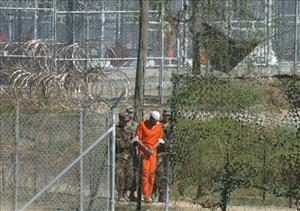 In this 2002 file photo, a detainee is escorted to interrogation by U.S. military guards at Camp X-Ray at Guantanamo Bay U.S. Naval Base, Cuba.