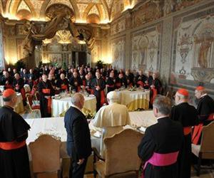 Pope Benedict XVI, center, delivers a blessing prior to a luncheon with Cardinals to mark the fifth anniversary of his election, in the Ducale Hall, at the Vatican, April 19, 2010.