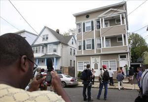 A local resident, left, and members of the media photograph a house in Bridgeport, Conn., where Faisal Shahzad worked.