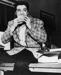 25th March 1958:  American singer and actor Elvis Presley (1935-1977) sitting on a bench eating a sandwich, Memphis, Tennessee.