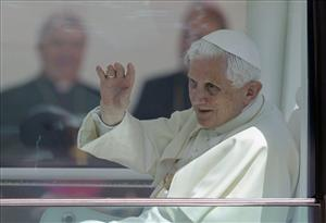 Pope Benedict XVI waves from the popemobile after arriving at Portela Airport for a four-day trip to Portugal on Tuesday, May 11, 2010.